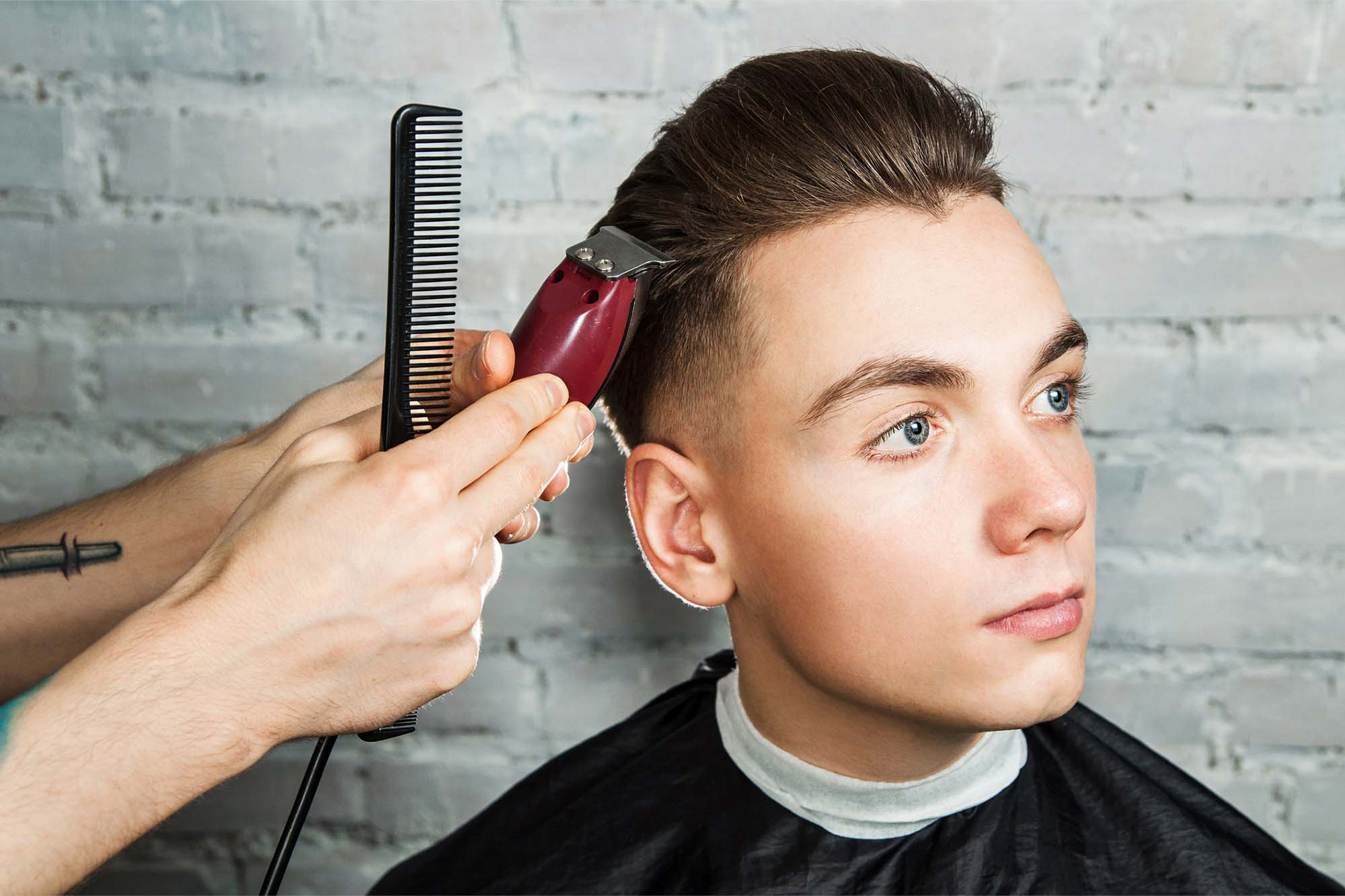 Barber hair styling of young guy
